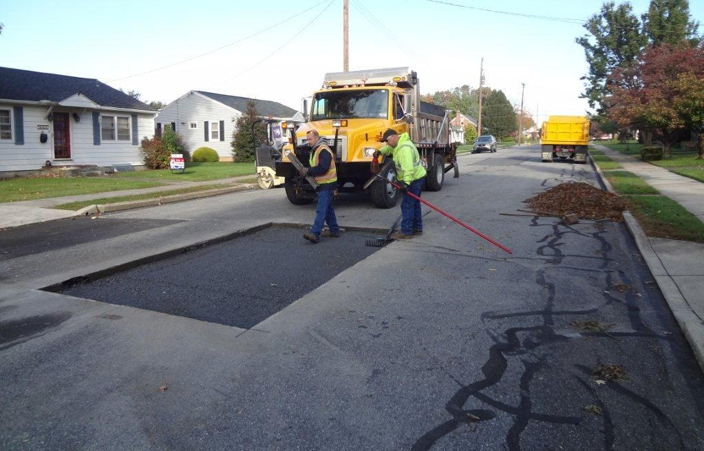 Construction crew sealing and patching a road